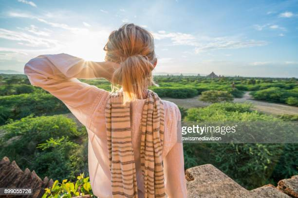 Traveler female contemplating the Bagan archeological zone at sunrise, Burma