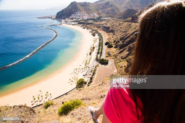 Traveler girl contemplating from viewpoint the beautiful Tenerife island with beach in a sunny day during travel vacations in the island.