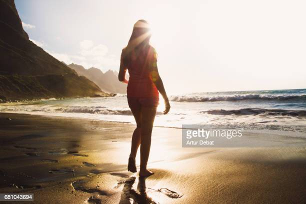 traveler girl enjoying the beach in tenerife island contemplating the stunning landscape with golden light during travel vacations in the canary islands with warm and sunny days. - canary islands stock photos and pictures