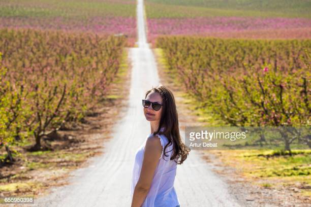 Traveler girl in front of a stunning long straight road between the blooming trees with pink flowers in a candid and idyllic place in the Catalonia countryside during springtime and warm and sunny weather.