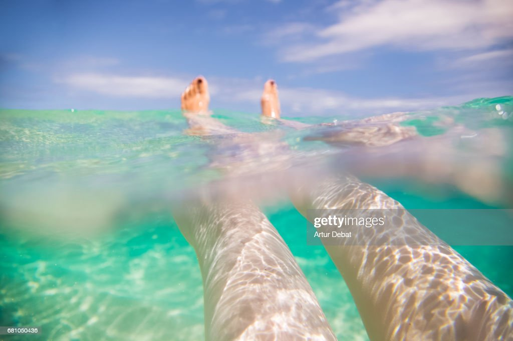Traveler girl swimming and enjoying alone the beautiful beach during travel vacations in the Fuerteventura island with nice water colors, relaxing moment in stunning place with underwater view. : Stock Photo