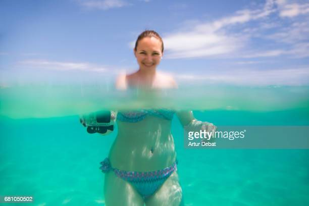 Traveler girl swimming and enjoying alone the beautiful beach during travel vacations in the Fuerteventura island with nice water colors, relaxing moment in stunning place with underwater view.