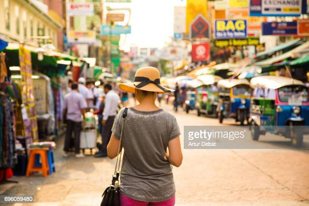 Traveler girl with hat protecting from strong sun in the bustle city of Bangkok during travel vacations.