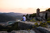 Traveler guy contemplating the view from the stunning Siurana town on top of cliff with amazing views during travel vacations in the Catalonia region.