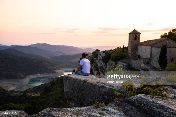 traveler guy contemplating the view from the stunning siurana town on top of cliff with amazing views during travel vacations in the catalonia region. - pueblo fotografías e imágenes de stock
