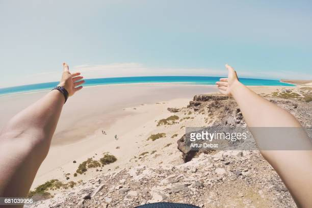 Traveler guy from personal perspective showing with open arms the beautiful beach in Fuerteventura island during travel vacations with warm and sunny days.