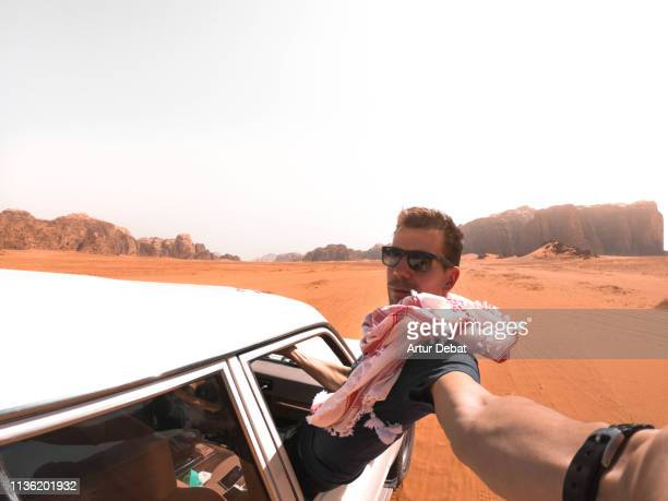 traveler guy taking a selfie from out of the car driving in the wadi rum desert. - jordan middle east stock pictures, royalty-free photos & images