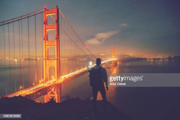 traveler guy with golden gate bridge at night. - san francisco bridge fotografías e imágenes de stock