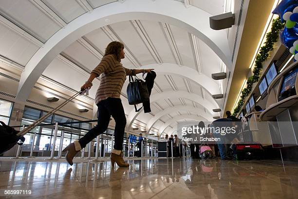 A traveler heads to the check–in kiosks at John Wayne Airport's new Terminal C in Orange County as she joins fellow travelers in route to their...