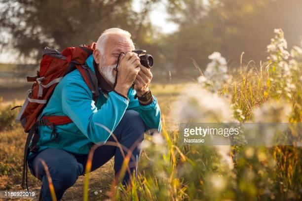 wanderer mann mit rucksack wandern in der nähe des sees fotografieren - fotografische ausrüstung stock-fotos und bilder