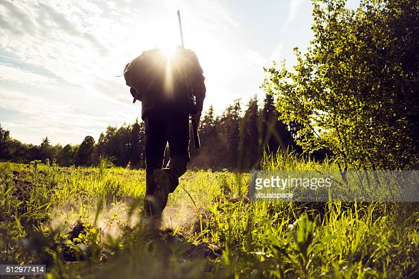 traveler hiking walking over a grassland - hunting sport stock pictures, royalty-free photos & images