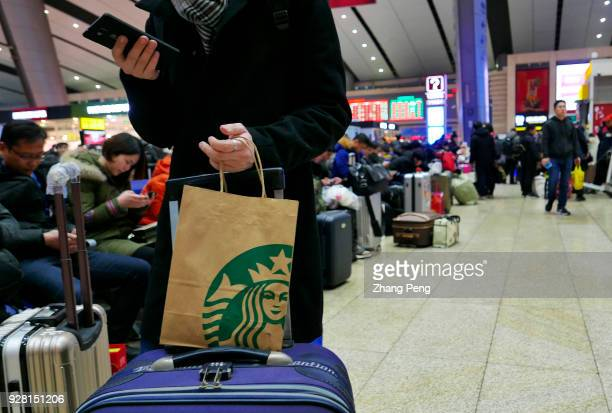 A traveler holds a bag printed with Starbucks logo in the railway station In 2017 the revenue of Starbucks China rose by 30% and till 2021 the total...