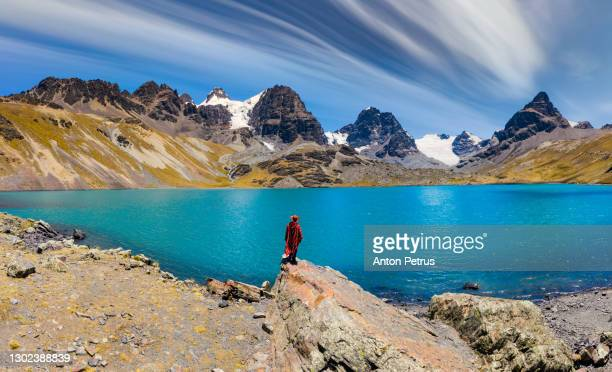 traveler in a poncho on the background of condoriri peak in cordillera real, andes, bolivia - bolivia stock pictures, royalty-free photos & images