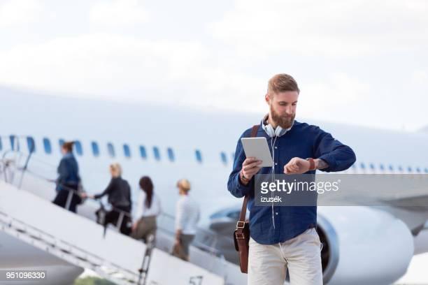 viajante na frente verificando o tempo de voo - ver a hora - fotografias e filmes do acervo