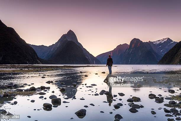 Traveler looking at view, Milford Sound, New Zealand