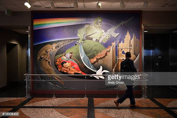 A traveler looks over a wall mural part of an installation at the Denver International Airport entitled Children of the World Dream Peace October 20...