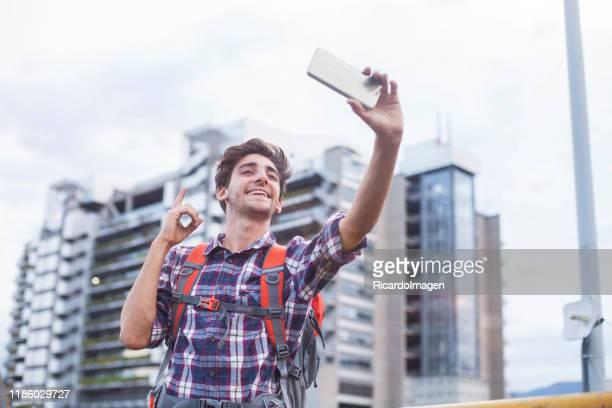 自分撮りを取るために彼の携帯電話を使用して旅行者の男 - コロンビア メデジン ストックフォトと画像