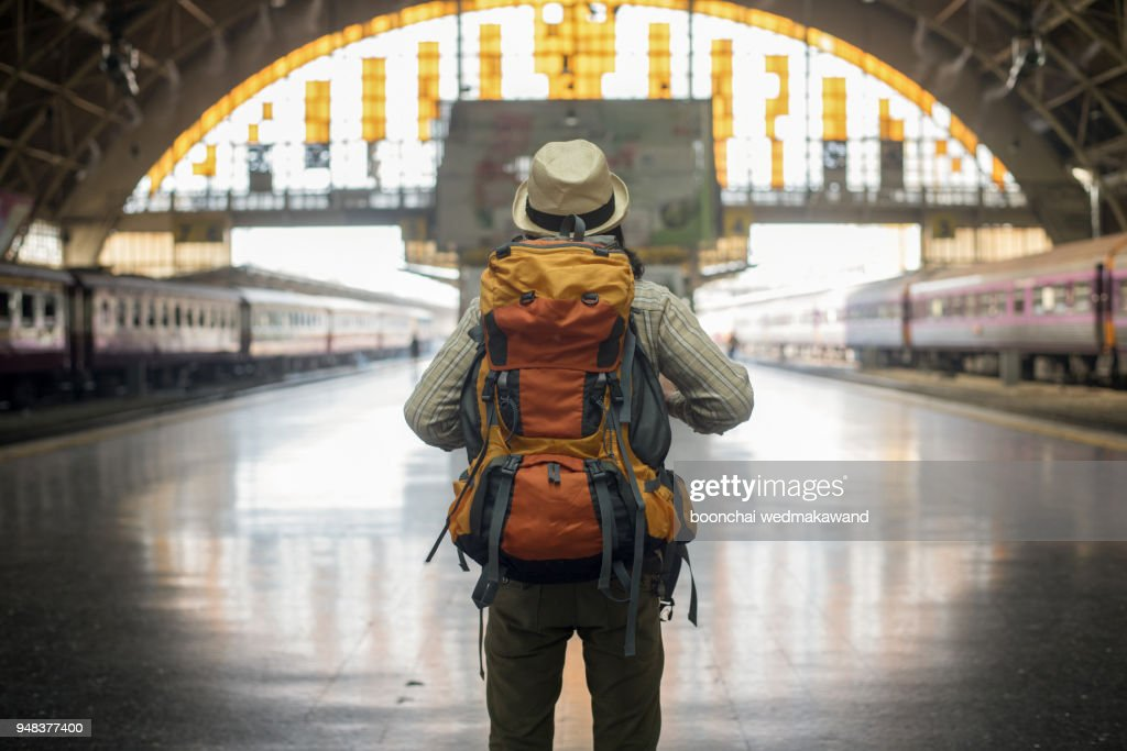 traveler man waits train on railway platform. : Stock Photo
