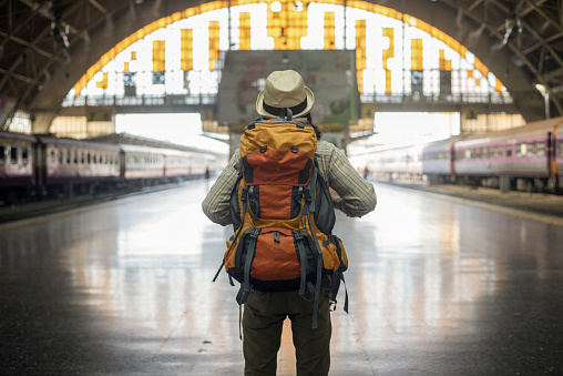 traveler man waits train on railway platform. - gettyimageskorea