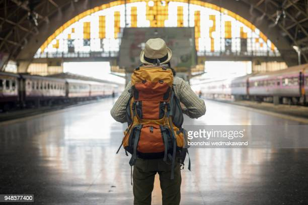 traveler man waits train on railway platform. - rucksacktourist stock-fotos und bilder