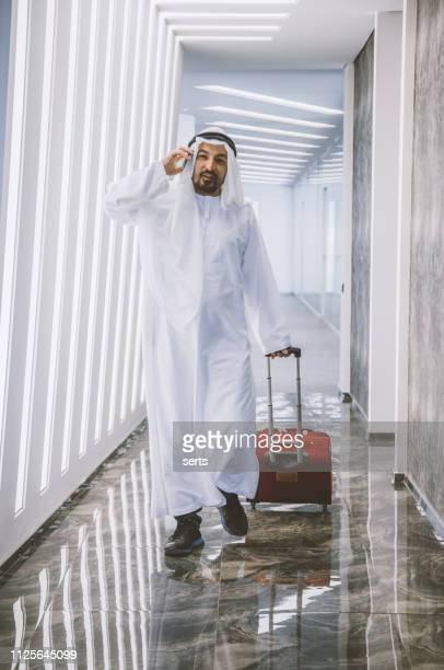 traveler middle eastern businesman carrying baggage walking to airplane in the airport - luggage stock pictures, royalty-free photos & images