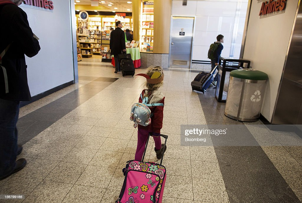 Traveler Nika Lysyj, 4, center, pulls a suitcase while walking with her father and brother to board a flight at LaGuardia Airport in the Queens borough of New York, U.S., on Wednesday, Nov. 21, 2012. U.S. travel during the Thanksgiving holiday weekend will rise a fourth straight year, gaining 0.7 percent from 2011, as trips by automobile rise even as airplane trips decline, AAA said last week. Photographer: Michael Nagle/Bloomberg via Getty Images