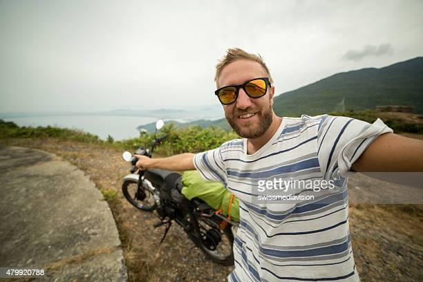 Voyageur moto sur la route en prenant un selfie