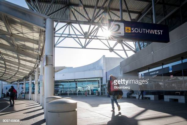 A traveler passes in front of Southwest Airlines Co signage at Oakland International Airport in Oakland California US on Friday Jan 19 2018 Southwest...