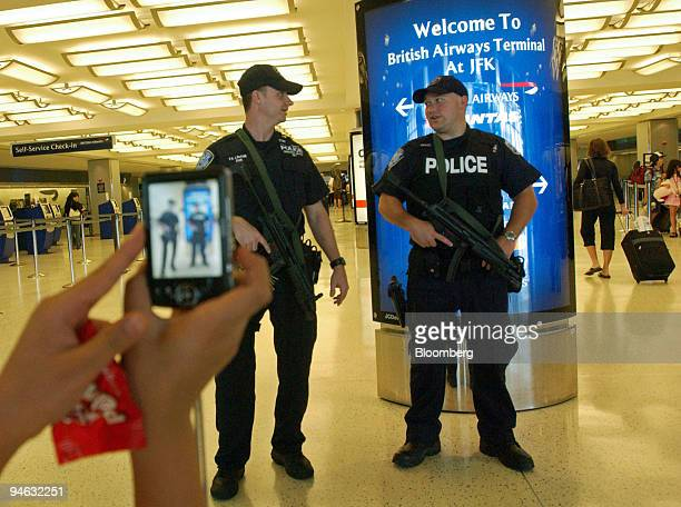 A traveler photographs heavily armed Port Authority police officers inside the British Airways terminal at John F Kennedy Airport in New York...