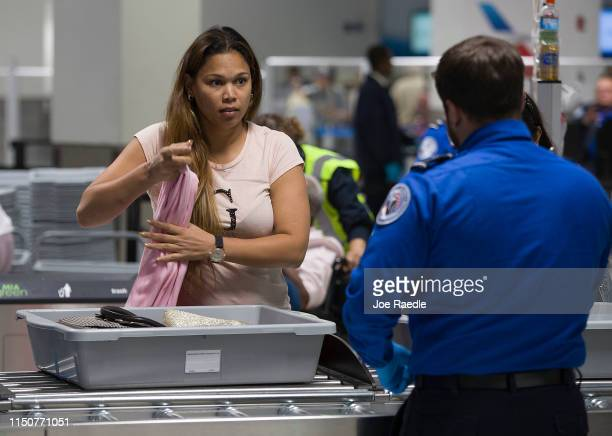 Traveler places her carry on items into a tray as a Transportation Security Administration agent helps her use the 3-D scanner at the Miami...