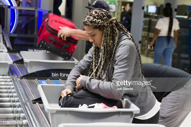 A traveler places her carry on items into a tray as a Transportation Security Administration agent helps her use the 3D scanner at the Miami...