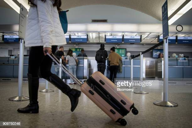 A traveler pulls a suitcase past an Alaska Air Group Inc checkin counter at the Oakland International Airport in Oakland California US on Friday Jan...