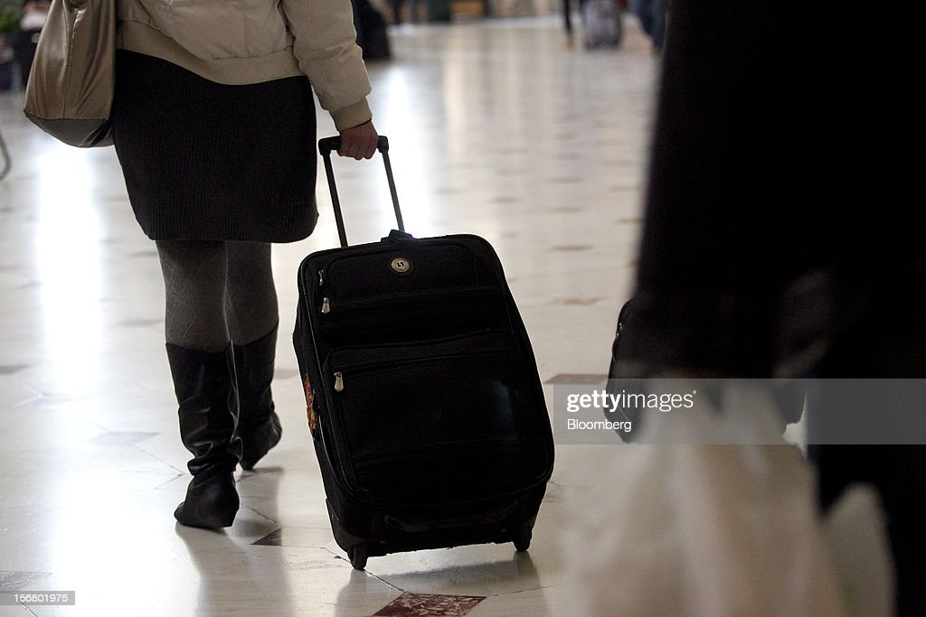 A traveler pulls a suitcase while walking out of Union Station in Washington, D.C., U.S., on Wednesday, Nov. 21, 2012. U.S. travel during the Thanksgiving holiday weekend will rise a fourth straight year, gaining 0.7 percent from 2011, as trips by automobile rise even as airplane trips decline, AAA said last week. Photographer: Andrew Harrer/Bloomberg