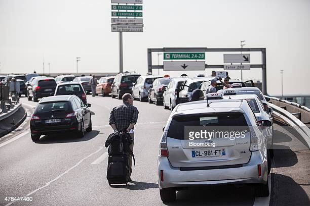 A traveler pulls his luggage past a row of French taxi cabs sat on a road outside Charles de Gaulle airport during a protest against Uber...
