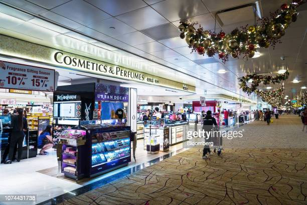 A traveler pushes a cart past duty free stores at Terminal 2 of Changi Airport in Singapore on Thursday Dec 13 2018 Singapore'sChangiAirport...