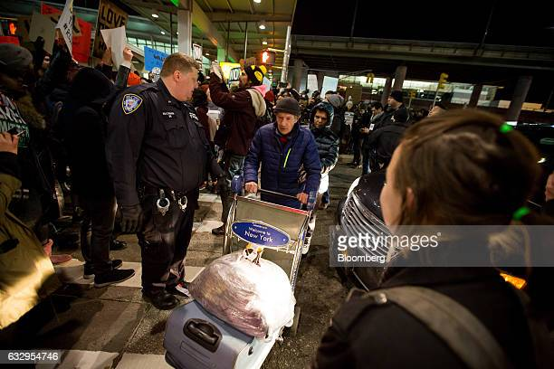 A traveler pushes a luggage cart past demonstrators protesting outside John F Kennedy International Airport against US President Donald Trump's...