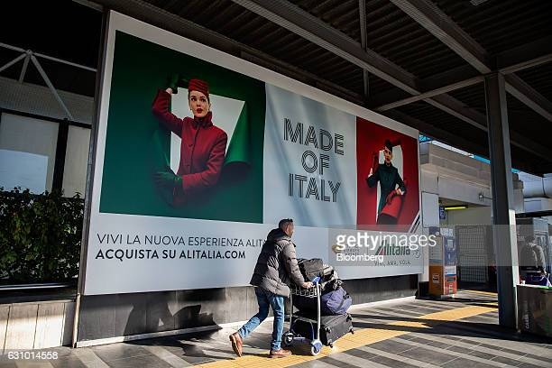 A traveler pushes a luggage trolley as he walks past an billboard advertising Alitalia SpA at Fiumicino airport in Rome Italy on Wednesday Jan 4 2017...