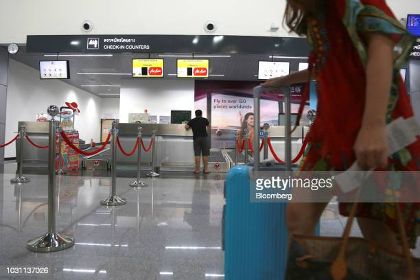 A traveler pushes a suitcase as a customer stands at an AirAsia Bhd checkin counter at the UTapao International Airport in Ban Chang district Rayong...
