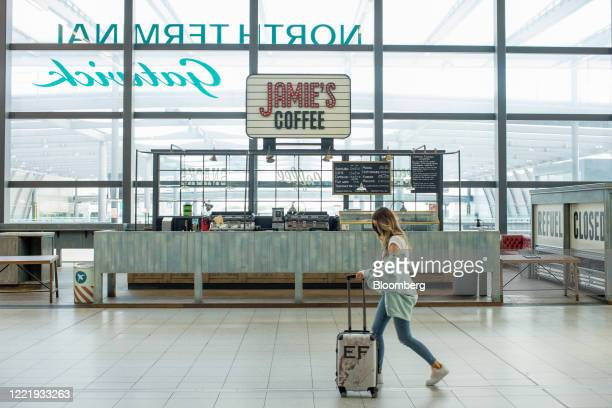 Traveler pushes a suitcase past a closed cafe near the check-in desks at London Gatwick Airport in Crawley, U.K., on Monday, June 22, 2020. European...