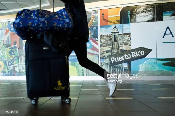 A traveler pushes luggage through Luis Munoz Marin International Airport in Carolina Puerto Rico on Sunday Jan 21 2018 Before Hurricane Maria struck...