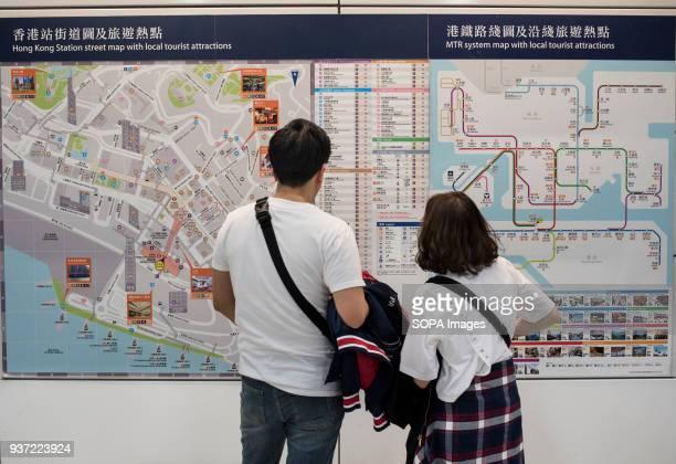 Traveler reading Hong Kong's MTR subway map
