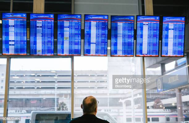 A traveler reads departures boards at Philadelphia International Airport during Winter Storm Quinn in Philadelphia Pennsylvania US on Wednesday March...
