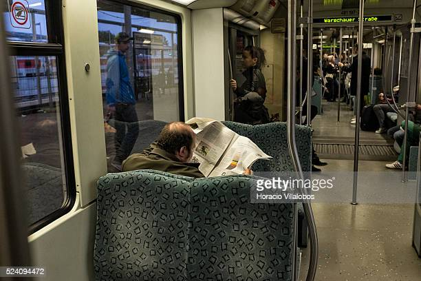 A traveler reads his newspaper while riding a SBahn train in Berlin Germany 13 April 2014 Berlin's SBahn 15 lines cover the city and its surrounding...