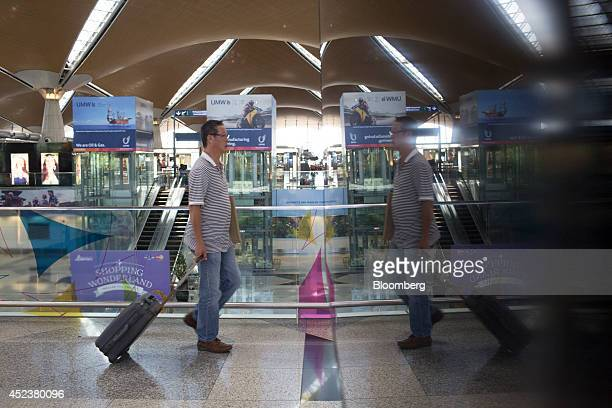 A traveler reflected on a surface walks through Kuala Lumpur International Airport in Sepang Malaysia on Saturday July 19 2014 Flags in Malaysia flew...