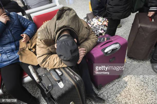 A traveler rests on suitcases while waiting in the main hall of the Shanghai Hongqiao Railway Station in Shanghai China on Monday Feb 12 2018 Almost...