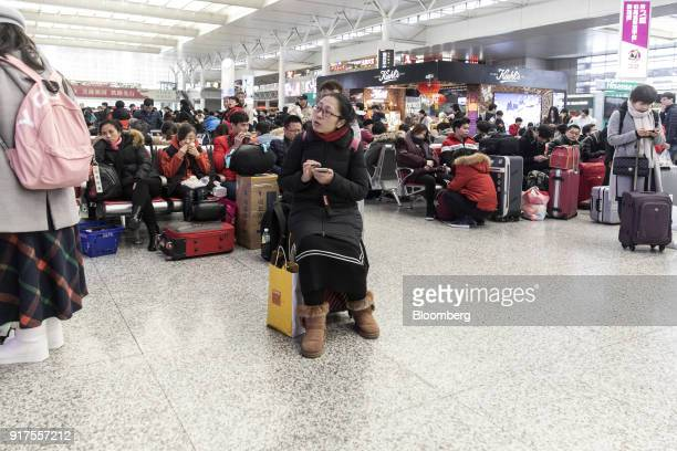 A traveler sits on a suitcase while waiting in the main hall of the Shanghai Hongqiao Railway Station in Shanghai China on Monday Feb 12 2018 Almost...