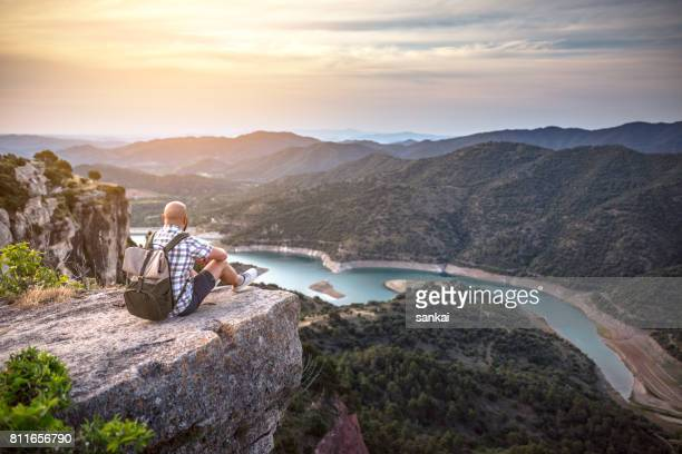 Traveler sits on the edge of a rock and enjoys the view of river in mountains