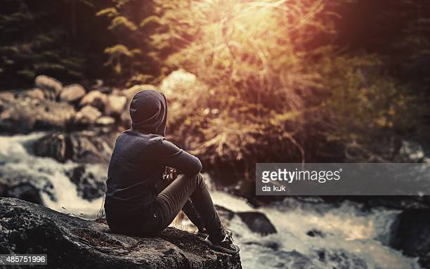 Traveler sitting in the forest near river