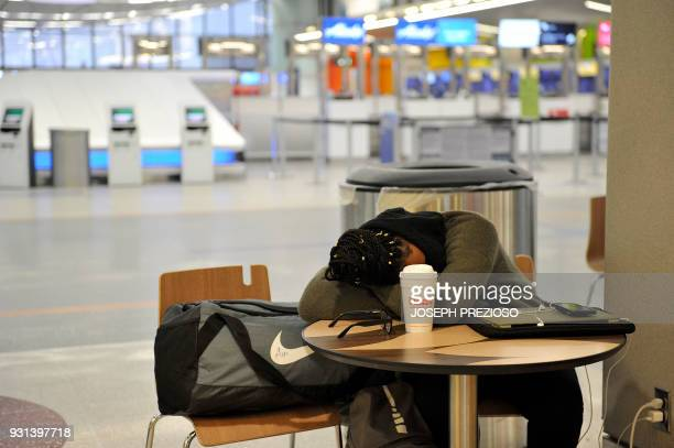 A traveler sleeps at a table with all flights canceled at Boston Logan Airport during a March noreaster on March 13 2018 / AFP PHOTO / Joseph...