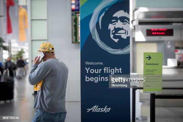 A traveler speaks on a mobile device next to Alaska Air Group Inc signage at the San Francisco International Airport in San Francisco California US...